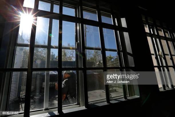 Charente LaGarde senior detention officer is viewed in the recreation yard through movie prop jail cell bars installed for a movie company that...