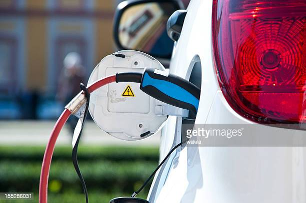 charge white electric car - hybrid car stock photos and pictures