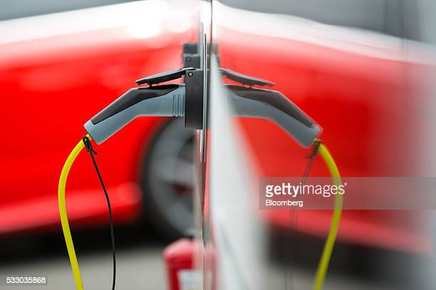 A charger for electric and hybrid automobiles sits at a charging station outside the Volkswagen AG factory in Wolfsburg Germany on Friday May 20 2016...