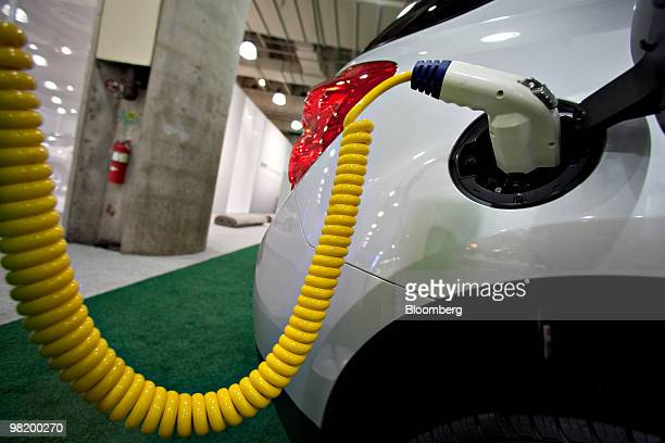 A charger sits plugged into a Chevrolet Equinox electric vehicle during a media preview of the New York International Auto Show in New York US on...