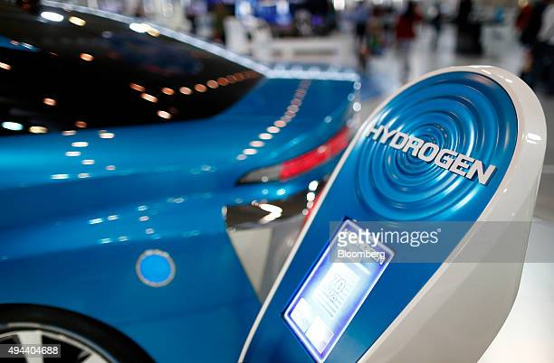 A charger stands on display next to a Toyota Motor Corp FCV Concept fuelcell vehicle at the company's showroom in Tokyo Japan on Tuesday Oct 13 2015...