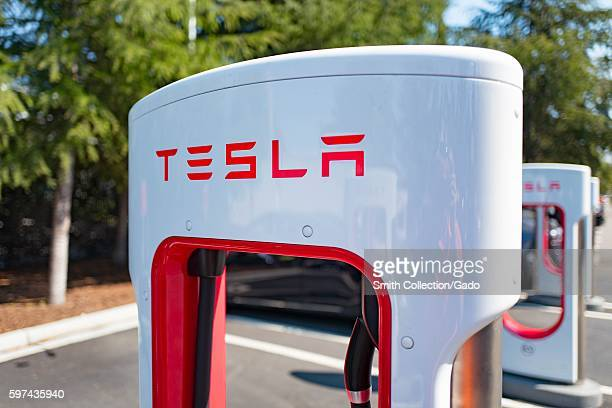 Charger with Tesla logo at a Supercharger rapid battery charging station for the electric vehicle company Tesla Motors in the Silicon Valley town of...