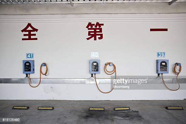 Chargers for electric vehicles hang on a wall at a charging station in Taiyuan Shanxi province China on Tuesday Sept 13 2016 Taiyuan became the first...