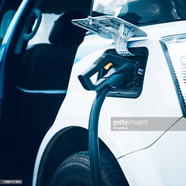 charging an electric car - hybrid vehicle stock pictures, royalty-free photos & images
