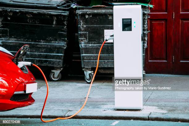 charging an electric car - hybrid car stock photos and pictures