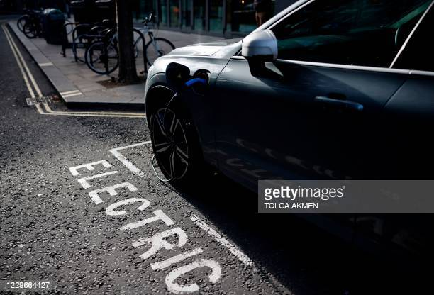 Charging cable is pictured plugged into a Volvo electric vehicle , parked in a parking bay reserved for electric vehicles, in London on November 18,...