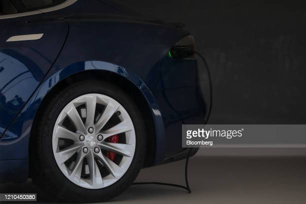 Charging cable sits plugged into a Tesla Model S in closed showroom in London, U.K. On Monday, April 20, 2020. European car sales dropped the most on...