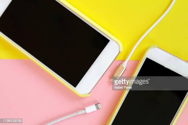 usb charging cables with smartphones in top view - aufladen stock-fotos und bilder