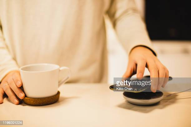 charging mobile phone battery with wireless charging device - plugging in stock pictures, royalty-free photos & images