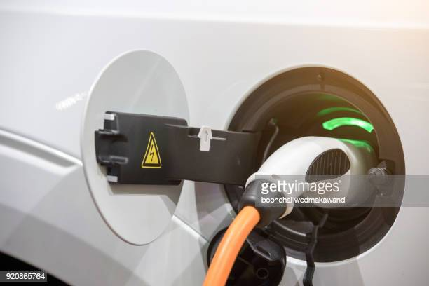 charging of an electric car - hybrid car stock photos and pictures