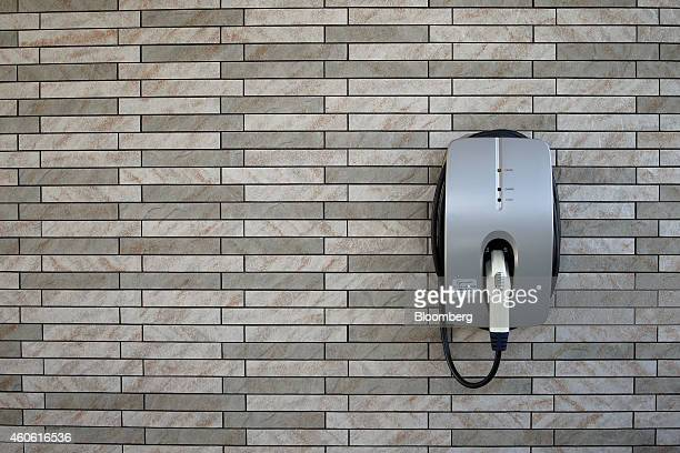 Charging plug for electric vehicles and plug-in hybrid vehicles is mounted to a wall outside a model smart home in Toyota Motor Corp's Ecoful Town in...