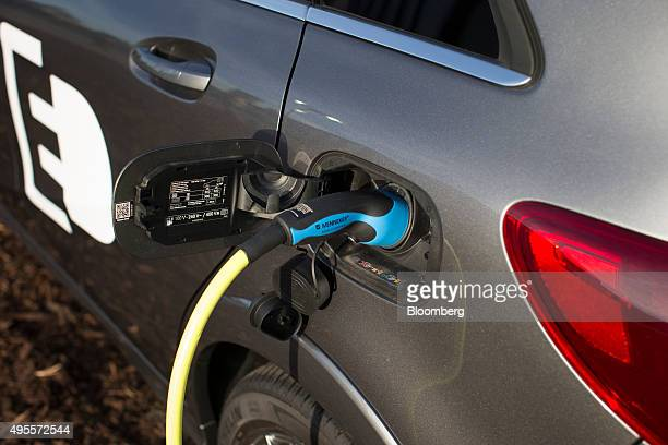 A charging plug produced by Mennekes Elektrotechnik GmbH sits connected to a MercedesBenz B class electric automobile produced by Daimler AG during a...