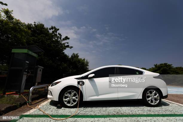 A charging plug sits connected to a General Motors Co Chevrolet 2017 Volt hybrid electric vehicle at a charging station in Jeju South Korea on...