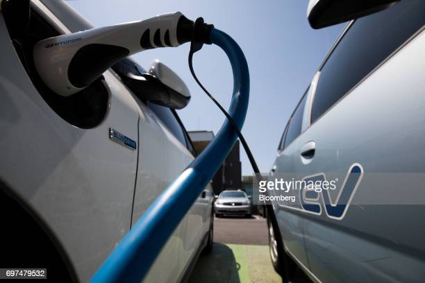 A charging plug sits connected to an electric vehicle at a charging station in Jeju South Korea on Thursday June 15 2017 The election ofMoon...