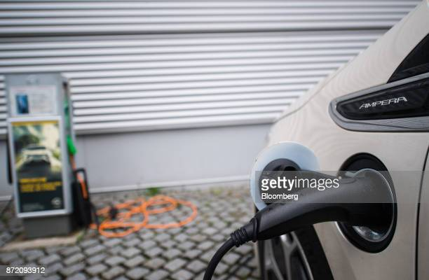 A charging plug sits connected to an Opel Ampera electric automobile outside the Adam Opel AG factory in Ruesselsheim Germany on Thursday Nov 9 2017...
