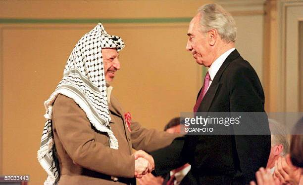Chariman Yasser Arafat shakes hands with Israeli Foreign Minister Shimon Peres 18 May 1994 at a ceremony honoring Norway's role in the Israeli-PLO...