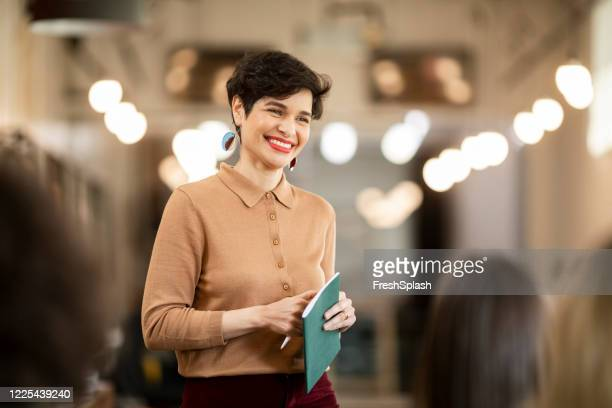charismatic businesswoman during a business coaching presentation at a modern company - attending stock pictures, royalty-free photos & images