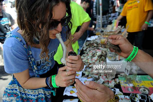 Charissa Claassen takes a hit off a pipe at the ITal Hempwick Booth during the High Times Cannabis Cup at Denver Mart in Denver Colorado on April 20...