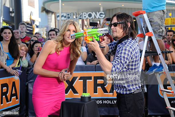 Charissa Thompson and Norman Reedus play around with a toy crossbow at 'Extra' at Universal Studios Hollywood on October 2 2014 in Universal City...