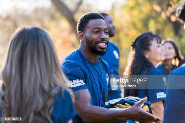 charity event organizer greets volunteer during community cleanup event - social responsibility stock pictures, royalty-free photos & images