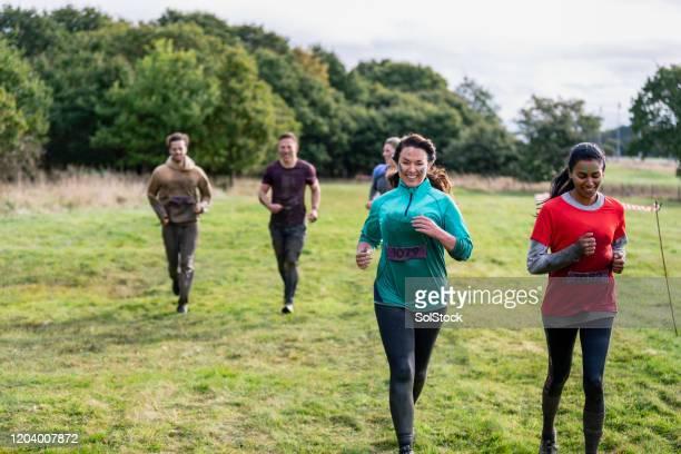 フィールドを越えて走るチャリティーイベント参加者 - 接近する 女性 ストックフォトと画像