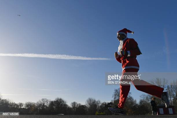 A charity runner dressed as Father Christmas participates in a 'Santa Run' charity fun run in Battersea Park in London on December 9 2017 Hundreds of...