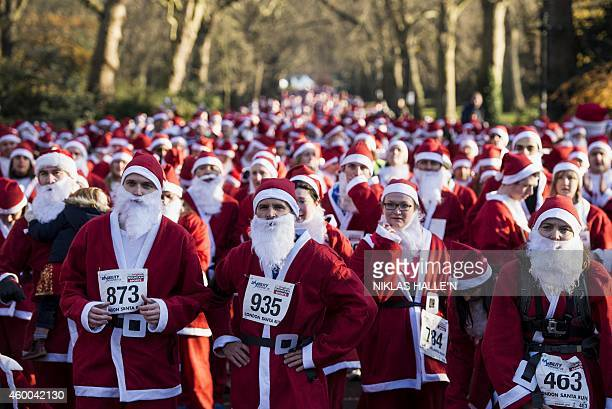 Charity runners dressed as Father Christmas await the start of the 'Santa Run' charity fun run in Battersea Park in London on December 6 2014...
