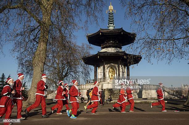 Charity runners dressed as Father Christmas participate in a 'Santa Run' charity fun run in Battersea Park in London on December 6 2014 Hundreds of...