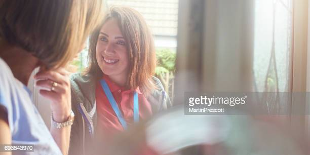 charity worker at the front door - knocking on door stock photos and pictures