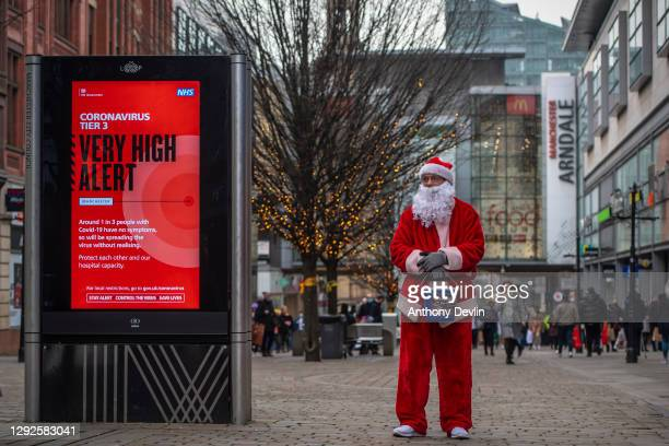 Charity worker from Help The Homeless dressed as Father Christmas collects donations on Market Street in Manchester city centre on December 22, 2020...