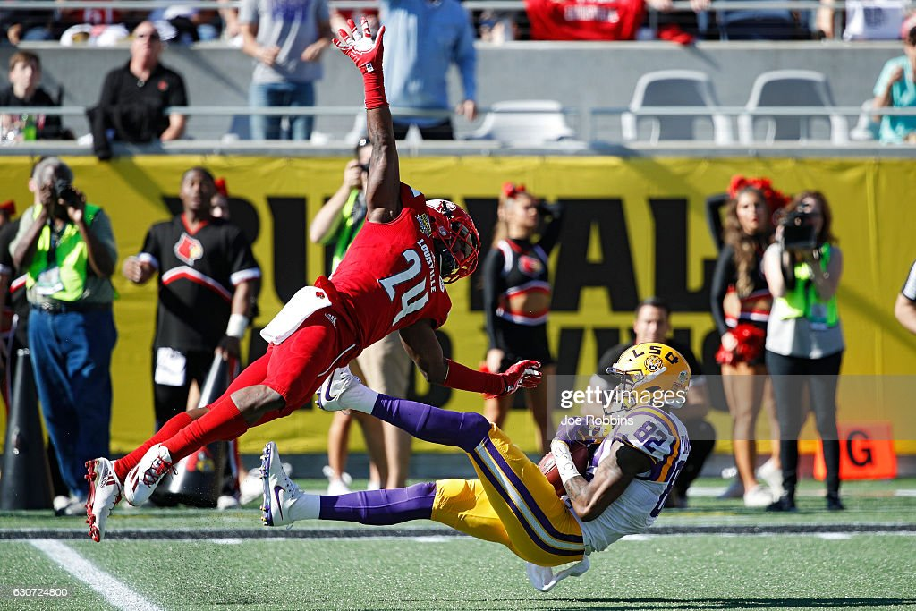 D.J. Chark #82 of the LSU Tigers makes a 39-yard reception behind Zykiesis Cannon #24 of the Louisville Cardinals to set up a touchdown in the second quarter of the Buffalo Wild Wings Citrus Bowl at Camping World Stadium on December 31, 2016 in Orlando, Florida.
