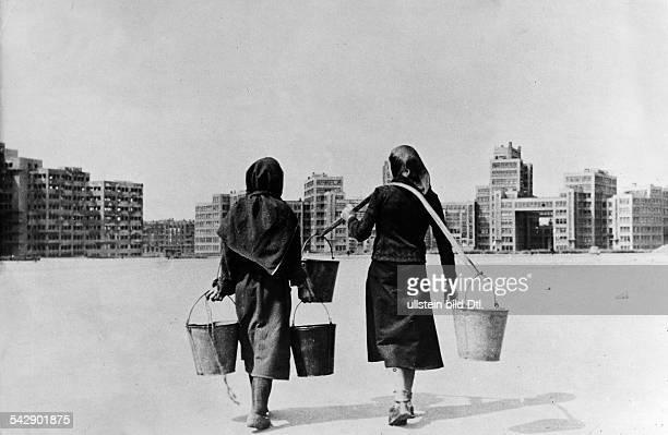 Charkow Dschersinskyplatz Zwei Frauen tragen jeweils zwei Eimer mit Wasser das sie von den oeffentlichen Pumpen geholt haben die Wasserversorgung ist...