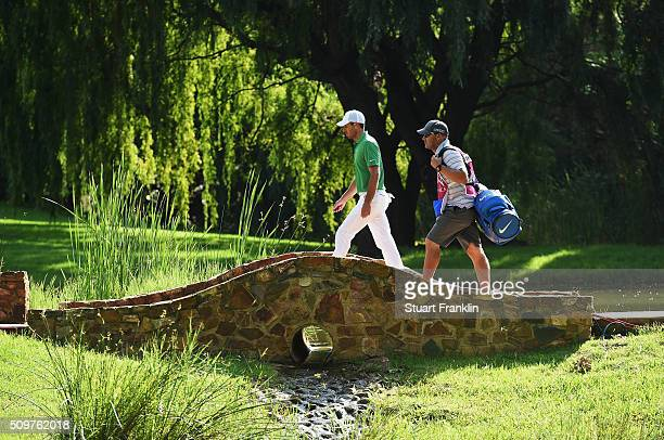 Charl Schwartzel of South Africa and caddie walk over a bridge during the second round of the Tshwane Open at Pretoria Country Club on February 12...