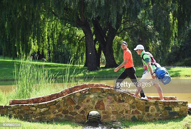 Charl Schwartzel of South Africa and caddie walk over a bridge during the third round of the Tshwane Open at Pretoria Country Club on February 13...