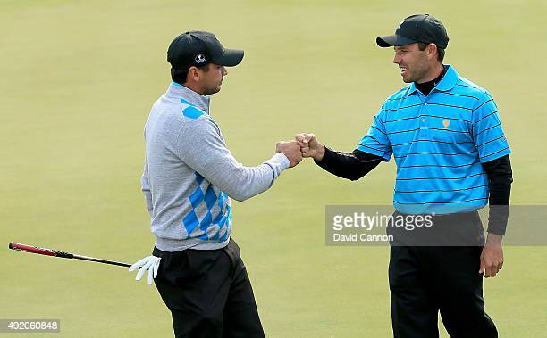 Charl Schwartzel of South Africa and the International Team congratulates his partner Jason Day of Australia after Day had holed a tricky birdie putt...