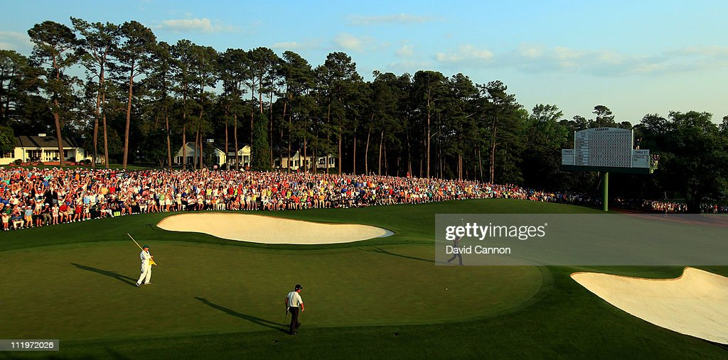 Charl Schwartzel of South Africa celebrates a birdie putt on the 18th green en route to his two-stroke victory as K.J. Choi of South Korea looks on at the 2011 Masters Tournament at Augusta National Golf Club on April 10, 2011 in Augusta, Georgia.