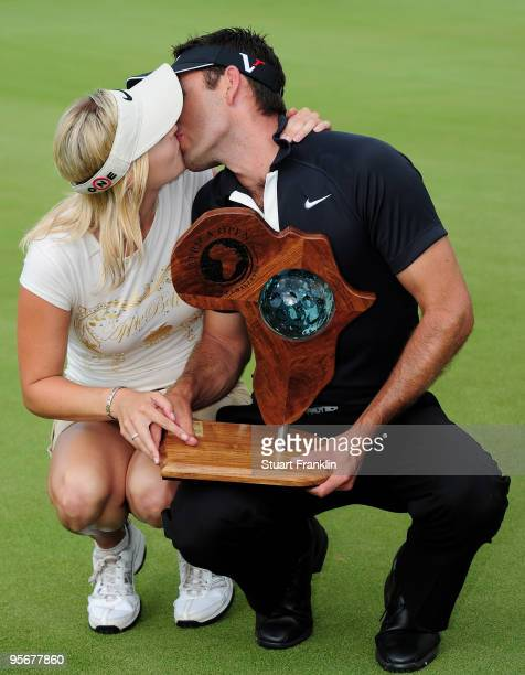 Charl Schwartzel of South Africa holds the winners trophy as he kisses his girlfriend Rosalind Jacobs after the final round of the Africa Open at the...