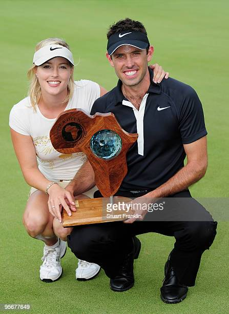 Charl Schwartzel of South Africa holds the winners trophy with his girlfriend Rosalind Jacobs after the final round of the Africa Open at the East...