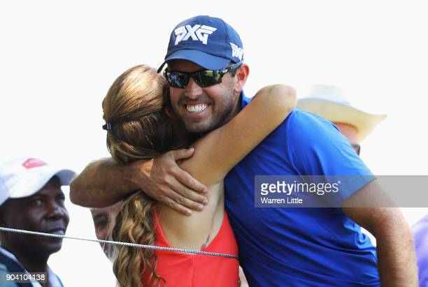 Charl Schwartzel of South Africa hugs a golf fan after hitting her with a ball on the 9th hole during day two of the BMW South African Open...