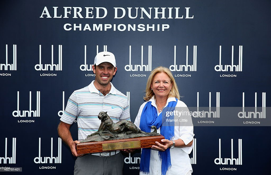 Charl Schwartzel of South Africa is presented the trophy by Gaynor Rupert, wife of Johann Rupert, CEO of Dunhill (R) after winning the Alfred Dunhill Championship on a score of -17 under par at Leopard Creek Country Club on December 1, 2013 in Malelane, South Africa.