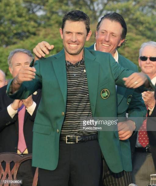 Charl Schwartzel of South Africa receives the Masters green jacket from Phil Mickelson of the United States after winning the tournament in Augusta...