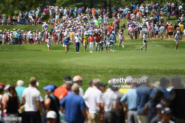 Charl Schwartzel of South Africa Rickie Fowler of the United States and Dustin Johnson of the United States walk on the fourth hole during the third...