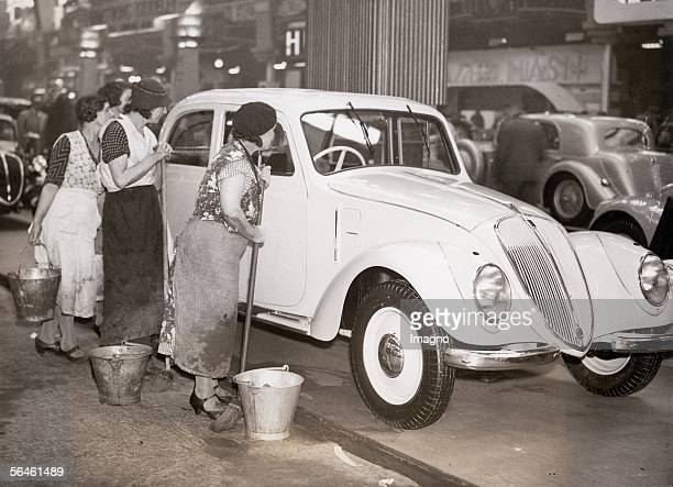 Charladies examining a luxury limousine at an automobile exhibition in London 1936 Photography 1936 [Putzfrauen begutachten eine LuxusLimousine bei...