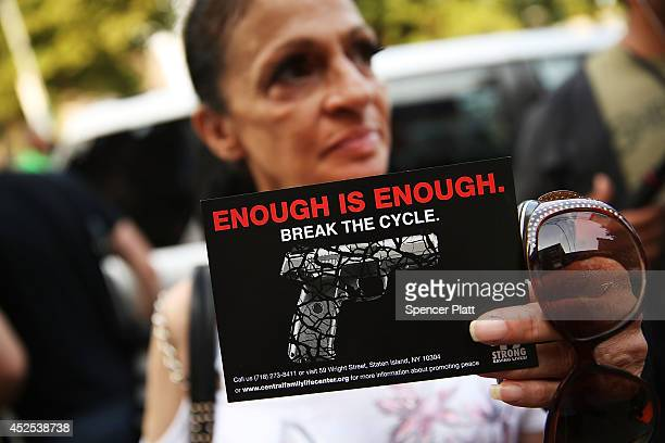 Charlene Thomas holds up a card while attending a vigil for Eric Garner near where he died after he was taken into police custody in Staten Island...
