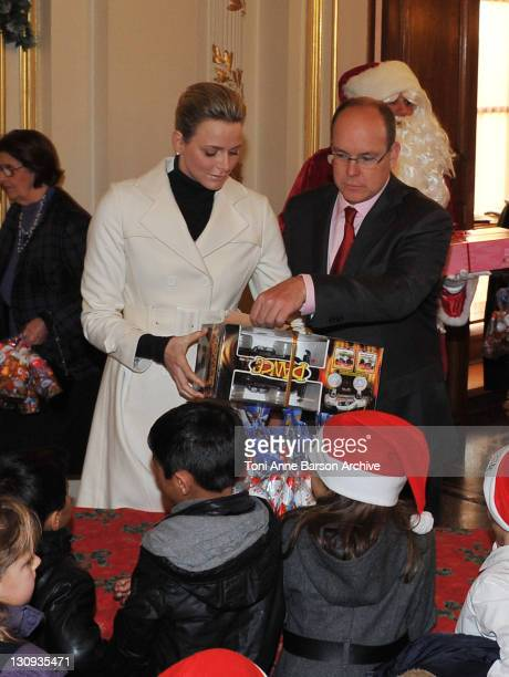 Charlene Wittstock and Prince Albert II of Monaco give away presents to children during the Monaco Christmas Tree at the Monaco Palace on December...
