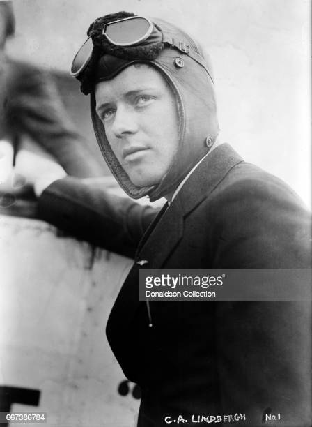 Charles A. Lindbergh wearing flight goggles next to a plane in circa 1920.
