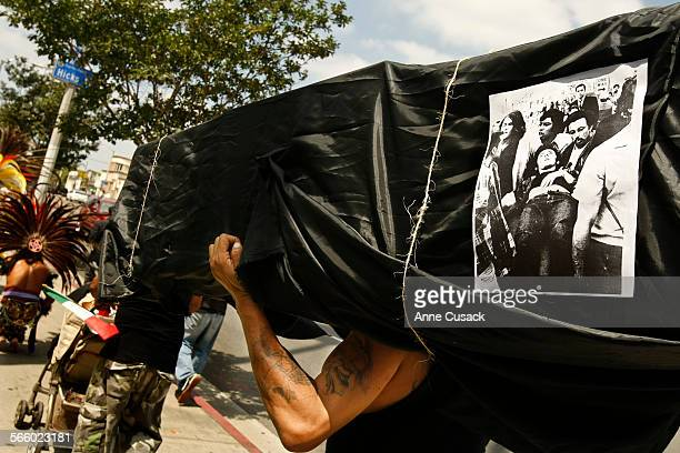 Charles Aguayo carries a coffin with a photo of a shooting victim from August 29 1970 as a march is held on Whittier Boulevard in East Los Angeles to...