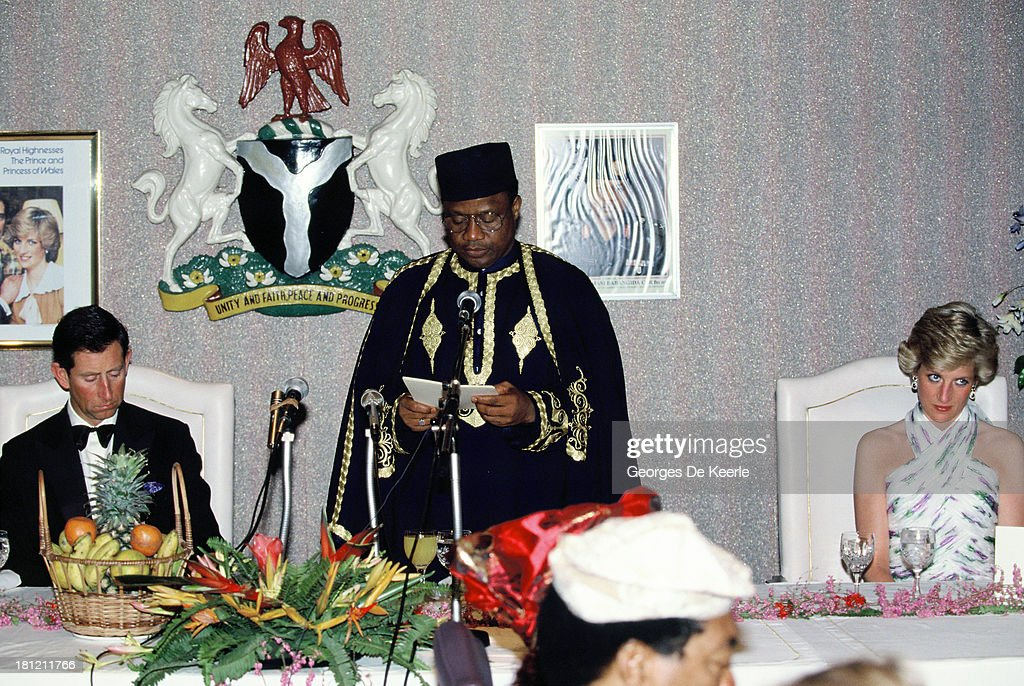 Charles (L) and Diana, Prince and Princess of Whales, attend a State Banquet with the former Nigerian president Ibrahim Babangida during their official visit to Nigeria on March 15, 1990 in Lagos, Nigeria. The princess wears a Catherine Walker dress.