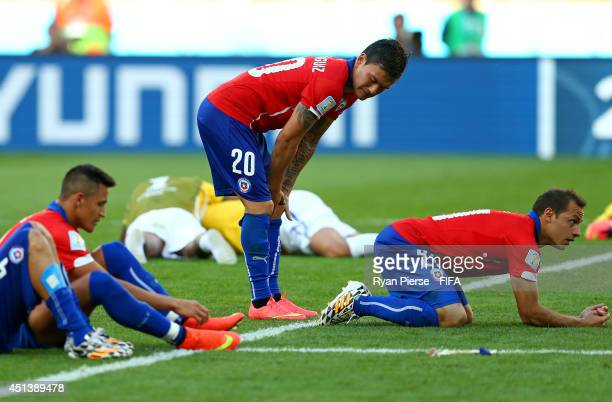 Charles Aranguiz and players of Chile react after the defeat in the 2014 FIFA World Cup Brazil Round of 16 match between Brazil and Chile at Estadio...