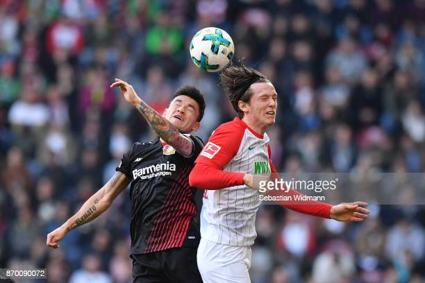 Charles Aranguiz of Bayer 04 Leverkusen and Michael Gregoritsch of Augsburg compete for the ball during the Bundesliga match between FC Augsburg and...